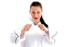 Young female chef holding cutlery Royalty Free Stock Photos