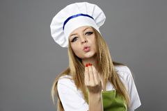Young female chef kissing her hand to show perfection over gray Stock Photo