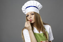 Young female chef kissing her hand to show perfection Stock Image