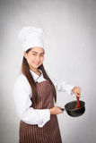 Young female chef with metal pot. In her hand Stock Photography
