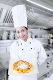 Chef cooks pizza. Young female chef is serving pizza stock image