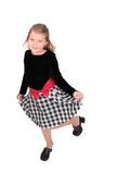 Young female child dancing. One young child in a black top and checkered dress dancing over white full length portrait Stock Image