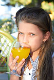 Young female child is drinking juice in outdoor ca Royalty Free Stock Images