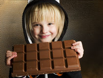 Young female child holding with both hands big chocolate bar in Royalty Free Stock Image