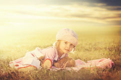 Young female child hugging a rabbit on a meadow - Retro look Royalty Free Stock Images
