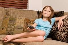 Young female child relaxing and watching television Royalty Free Stock Photo