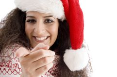 Young female with christmas hat pointing at camera Royalty Free Stock Photos