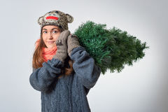 Young female with a christmas tree. Young female holding a christmas tree in her hands Stock Photo