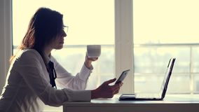 A young female clerk, office worker browses social networks on a mobile phone, during her short coffee break, rest in stock video