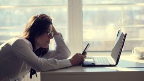 A young female clerk office worker browses social networks on a mobile phone, during her work day, in an office. a short
