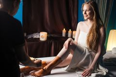 Young female client getting spa treatment in rejuvenation clinic. Mud therapy. Young woman getting spa treatment in healthcare clinic. Beautiful girl with loose stock photography