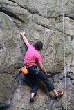 Young female climber climbing a route on a rock. Sokoliki, Poland. Stock Image