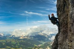 Young female climber on a vertical and exposed rock wall. Young female climber on a vertical and exposed Via Ferrata in the Italian Dolomites Royalty Free Stock Photography