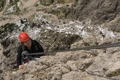 Young female climber on a Via Ferrata in the South Tyrol. Young female climber wearing a red helmet in the Dolomites in the South Tyrol in the Italian Alps Stock Photography
