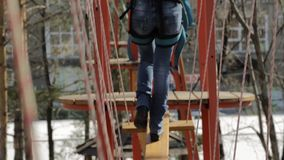 Young female climber walks by pendant log bridge on high ropes course in extreme park stock video