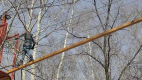 Young female climber walks by pendant log bridge on high ropes course in extreme park stock video footage