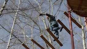 Young female climber walks by pendant log bridge on high ropes course in extreme park stock footage