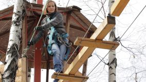 Young female climber walks by pendant log bridge on high ropes course in extreme park. Rock climbing concept. stock video