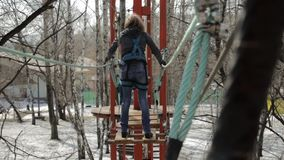 Young female climber walks by pendant log bridge on high ropes course in extreme park. Rock climbing concept. stock footage