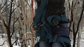 Young female climber walks by pendant rope bridge on high ropes course in extreme park. Rock climbing concept stock video