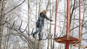 Young female climber walks by pendant rope bridge on high ropes course in extreme park. Rock climbing concept stock footage
