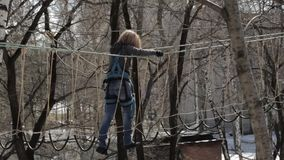 Young female climber walks by pendant rope bridge on high ropes course in extreme park. Rock climbing concept stock video footage