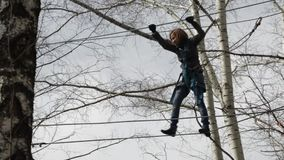 Young female climber walks by pendant rope bridge on high ropes course in extreme park. Rock climbing concept