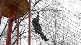 Young female climber walks by rope mesh bridge on high ropes course in extreme park stock video