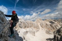 Young female climber wearing a red helmet and dressed in black on an exposed Via Ferrata. In the Dolomites in the South Tyrol in Italy with a great view behind Royalty Free Stock Image