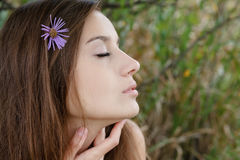 Young female closeup eyes closed. Profile of gorgeous young female with eyes closed and flower in her hair Stock Images