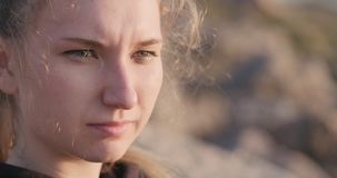 Young female closeup portrait sitting on a seashore with thoughtful look stock photography