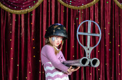 Young Female Clown in Helmet Aiming Large Rifle Royalty Free Stock Photos