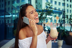 Young female with cocktail in her hand cheerfully speaking on th Royalty Free Stock Photo