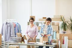 Young female colleagues standing by desk while making parcels for clients. Young female colleagues standing by desk while making parcels for their online clients royalty free stock photography