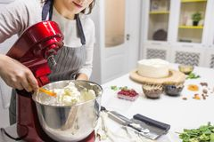 Young female confectioner whips cream in a metal bowl in a red electric mixer. The concept of homemade pastry, cooking. stock photos