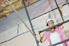 Young female construction worker climbing on scaffold Stock Photography