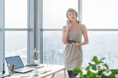 Young female consultant having business call in office at her workplace. Secretary speaking on the smart phone, holding Stock Image