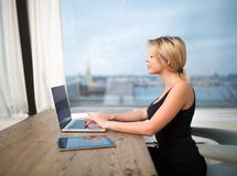 Young female content manager using modern laptop computer. Hipster girl chatting. Blonde woman successful freelance social media content writer keyboarding on Stock Photo