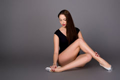 Young female contortionist in black bodysuit on dark background Royalty Free Stock Image