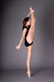 Young female contortionist dances, on dark background Royalty Free Stock Photos