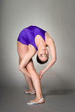 Young female contortionist performs, on dark background. Young female contortionist, in purple leotard, on dark background Royalty Free Stock Photography