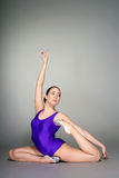 Young female contortionist in purple leotard on dark background Stock Photography