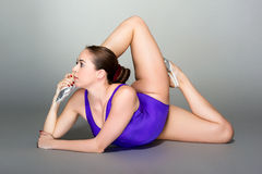 Young female contortionist in purple leotard on dark background. Young female contortionist, on dark gray background Royalty Free Stock Image