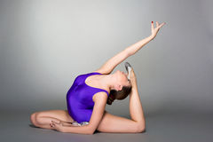 Young female contortionist in purple leotard on dark background Royalty Free Stock Images