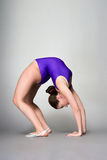 Young female contortionist in purple leotard on dark background Royalty Free Stock Photos