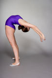 Young female contortionist in purple leotard on dark background Stock Images