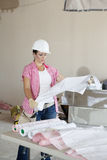 Young female contractor analyzing blueprints Stock Photo