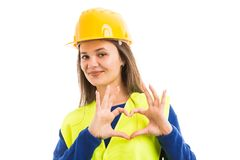 Young female contructor showing heart sign. Young female constructor or engineer showing heart sign with hands as building industry love concept isolated on royalty free stock images