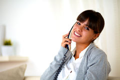 Young female conversing on phone looking at you Royalty Free Stock Photos