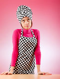 Young female cook against gradient Stock Images